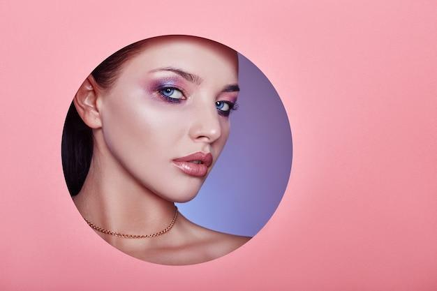Belles lèvres dodues de couleur rose vif, la femme regarde dans du papier rose coloré par un trou de cercle, un salon de beauté. maquillage, soins du visage publicitaires, lèvres parfaites, maquillage beauté mode et cosmétiques