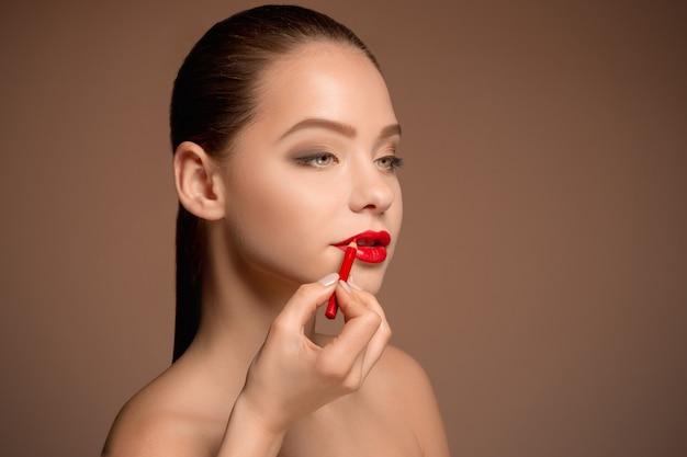 Belles lèvres féminines avec maquillage et pinceau