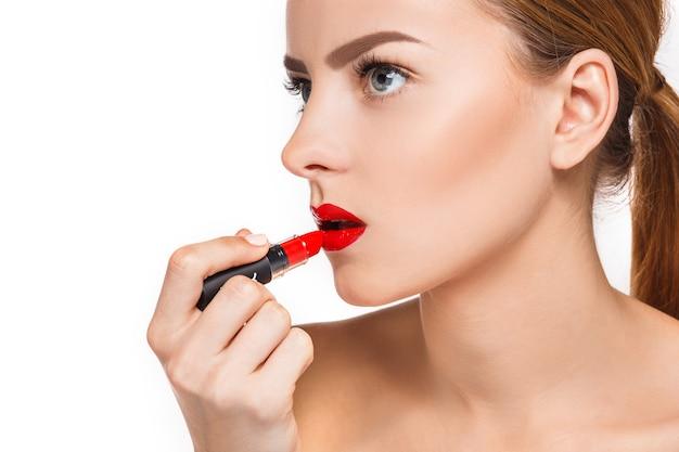 Belles lèvres féminines avec maquillage et pommade rouge sur blanc. processus de travail du maquilleur