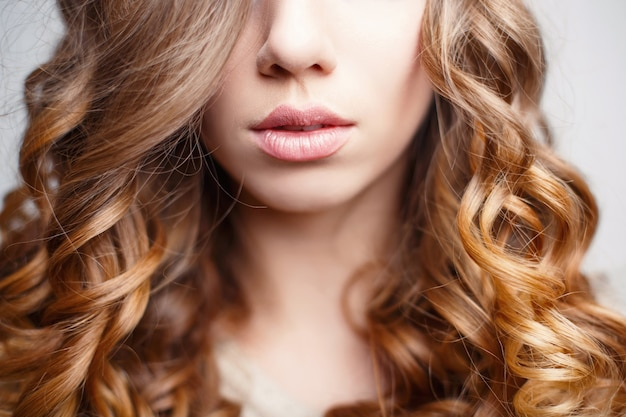 Belles lèvres roses de fille aux cheveux bouclés