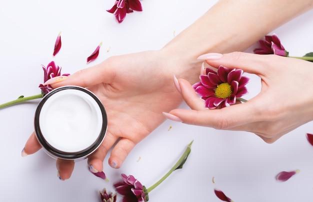 Belles mains féminines, crème et fleurs