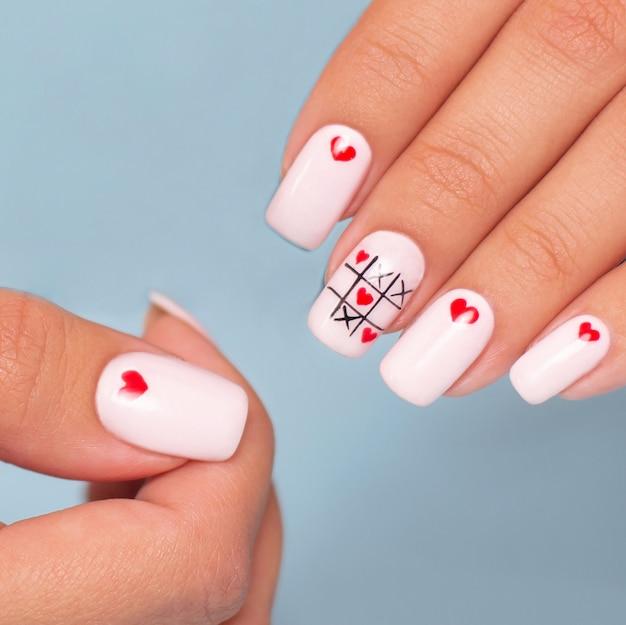 Belles mains féminines avec manucure créative, conception de coeurs