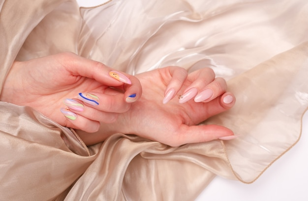 Belles mains féminines avec manucure d'été