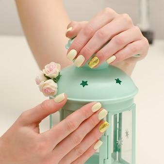 Belles mains féminines avec une manucure et une lampe-chandelier sur un fond clair. jaune avec des clous en or