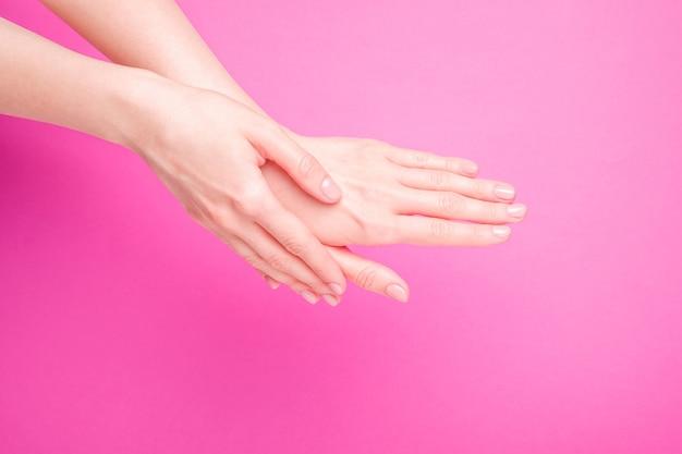 Belles mains féminines montrant la manucure mignonne fraîche, le concept de soins de la peau et des ongles, fond rose