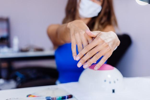 Belles mains féminines traitement des ongles des doigts processus de fabrication foreuse à ongles professionnelle en action concept de soins de beauté et des mains