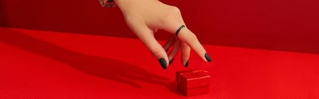 Belles mains de femme soignées avec boîte-cadeau sur fond rouge concept de vente shopping halloween