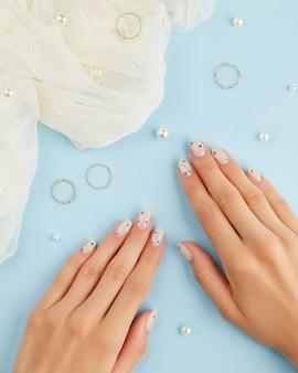 Belles mains de femme soignées avec un design d'ongle d'été sur fond bleu