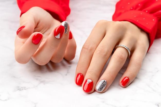 Belles mains de femme soignées avec un design d'ongles hristmas sur fond de marbre