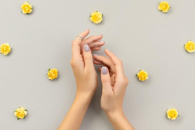 Belles mains de femme toilettée avec un design d'ongle minimal sur gris