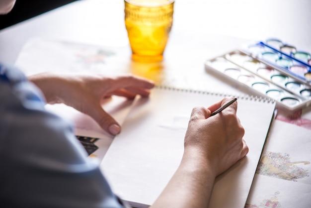 Les belles mains des femmes peignent avec un dessin à l'aquarelle au pinceau.
