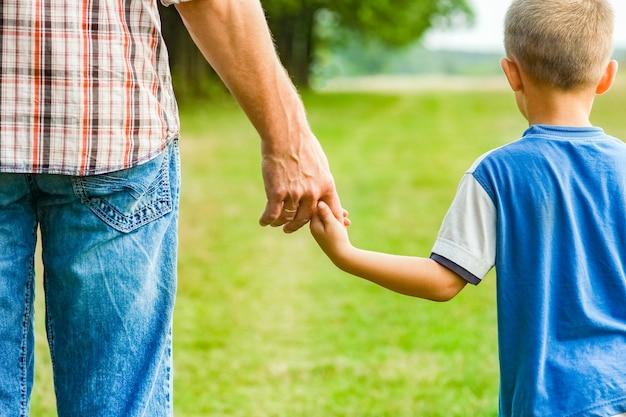 Belles mains de parent et enfant à l'extérieur dans le parc