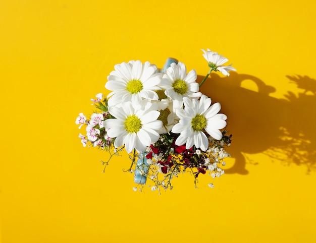 Belles marguerites dans un vase sur la table jaune