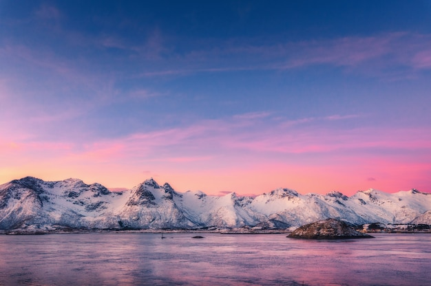 Belles montagnes couvertes de neige et ciel coloré reflété dans l'eau au crépuscule. paysage d'hiver avec mer, rochers enneigés, ciel violet, reflet, au coucher du soleil.