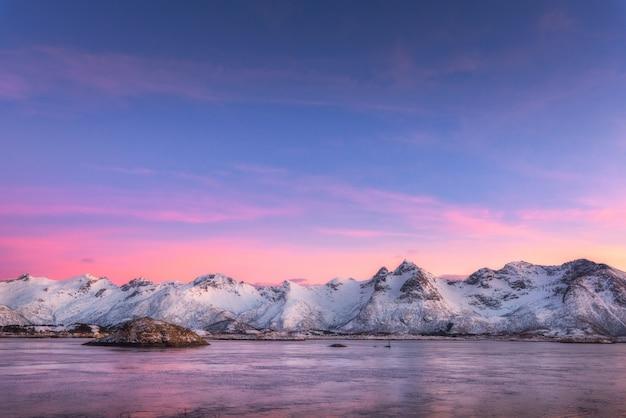 Belles montagnes couvertes de neige et ciel coloré reflété dans l'eau la nuit