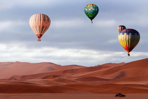 Belles montgolfières colorées et nuages spectaculaires au-dessus des dunes de sable dans le désert du namib