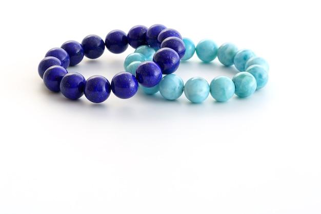 Belles perles de lapis lazuli bleu royal et bleu clair larimar ou pierre de stefilia en bracelets sur fond blanc