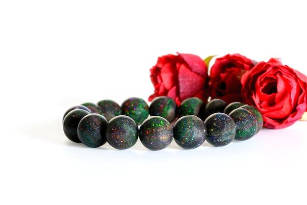 Belles perles d'opale noire rares en bracelet sur fond blanc