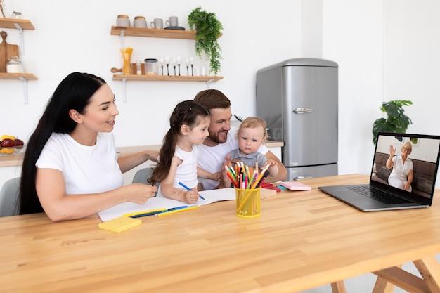 Belles personnes ayant un appel vidéo avec leur famille à la maison