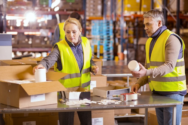 Belles personnes sérieuses debout autour de la table en emballant les boîtes