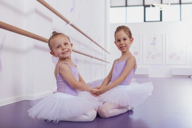 Belles petites ballerines se tenant la main, assis sur le sol à l'école de ballet, souriant à la caméra