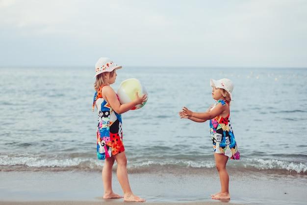 Belles petites filles adorables ensemble portrait féminin décontracté mode de vie beauté filles joyeuses tenant par la main sur le jeu de plage de la mer concept d'enfance