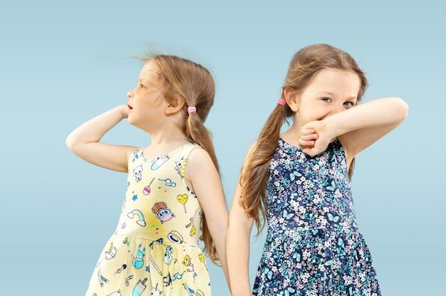 Belles petites filles émotionnelles isolées sur l'espace bleu