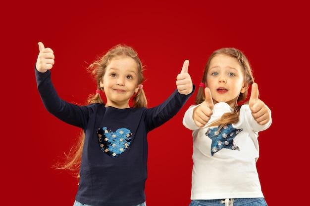 Belles petites filles émotionnelles isolées sur l'espace rouge. portrait demi-longueur de sœurs ou d'amis heureux pointant vers le haut