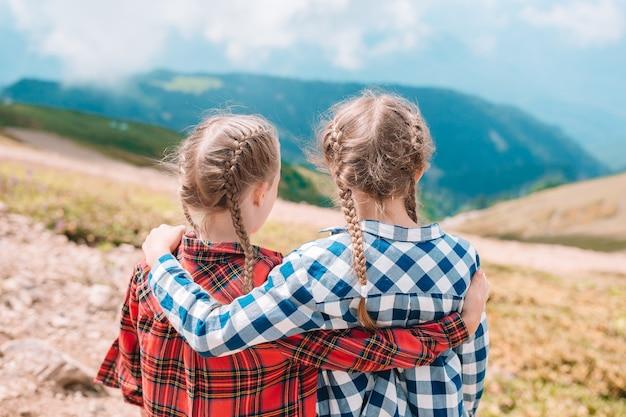 Belles petites filles heureuse dans les montagnes en arrière-plan du brouillard