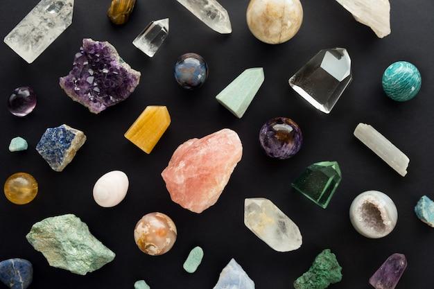 Belles pierres de cristal sur fond noir. pierres précieuses et cristaux colorés sur fond sombre. contexte des minéraux curatifs pour la relaxation et la méditation. mise à plat. vue de dessus