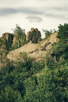 Belles pierres en forme de deux personnes au sommet d'une montagne entourée de verdure. nuage pluvieux en forme de halo au-dessus des têtes de pierre.