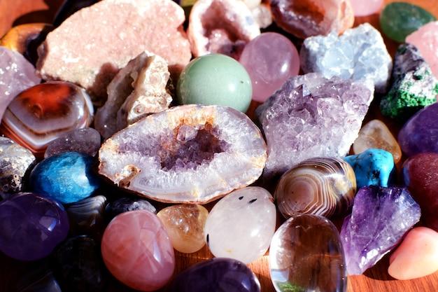 Belles pierres précieuses, améthyste géode et druses d'améthyste minérale violette naturelle sur un fond en bois. améthystes et quartz rose. gros cristaux de pierres semi-précieuses.
