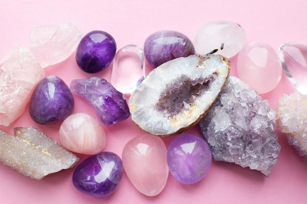 Belles pierres précieuses, améthyste géode et druses d'améthyste minérale violette naturelle sur fond rose. améthystes et quartz rose. gros cristaux de pierres semi-précieuses.