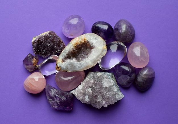 Belles pierres précieuses, améthyste géode et druses d'améthyste minérale violette naturelle sur fond violet. améthystes et quartz rose. gros cristaux de pierres semi-précieuses.
