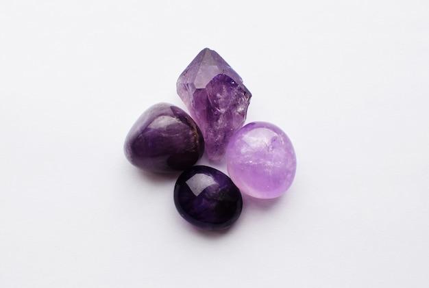 Belles pierres précieuses d'améthyste minérale violette naturelle sur fond blanc. gros cristaux de pierres semi-précieuses.