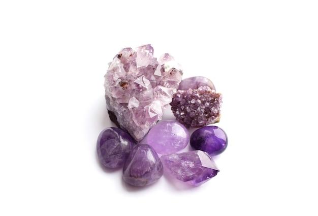 Belles pierres précieuses et druses d'améthyste minérale violette naturelle sur fond blanc. gros cristaux de pierres semi-précieuses.