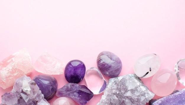 Belles pierres précieuses et druses d'améthyste minérale violette naturelle sur fond rose. améthystes et quartz rose. gros cristaux de pierres semi-précieuses.
