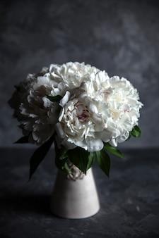 Belles pivoines sur fond de béton gris. mariage, anniversaire, saint valentin, cadeau ou concept de jour de la femme. rencontres saint-valentin
