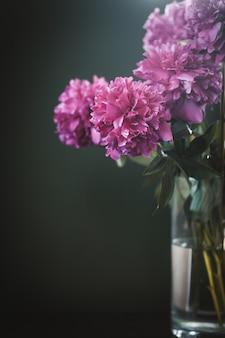 Belles pivoines roses dans un grand vase transparent sur vert