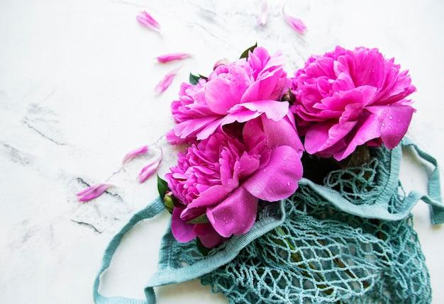 Belles pivoines roses dans un sac à cordes à la mode sur une surface en marbre blanc