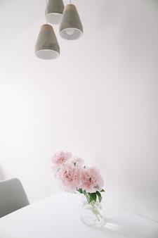 Belles pivoines roses dans un vase en verre à l'intérieur blanc minimal