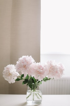 Belles pivoines roses dans un vase en verre sur une table blanche près d'une fenêtre