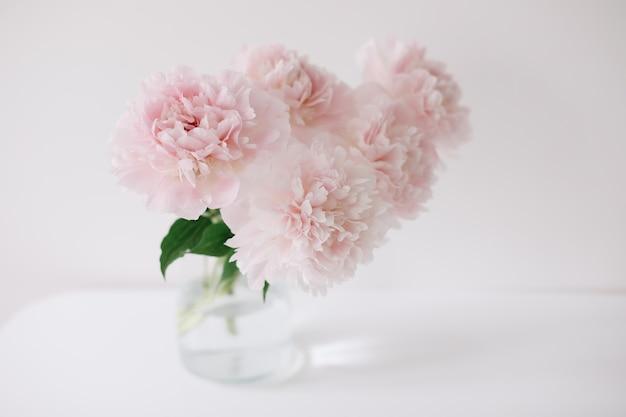 Belles pivoines roses fraîches dans un vase à l'intérieur de la maison