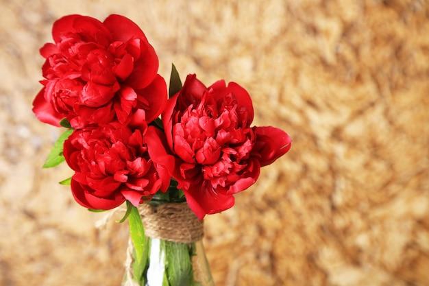 Belles pivoines roses sur la surface du mur marron