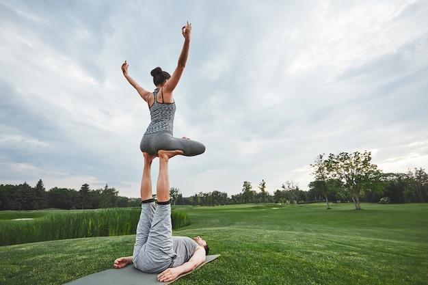 Belles poses avec un homme fort partenaire allongé sur un tapis et une femme en équilibre dans