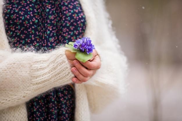 Belles premières fleurs de printemps de perce-neige dans les mains d'une jeune femme en cardigan blanc dans une forêt