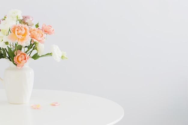 Belles roses dans une cruche blanche en céramique