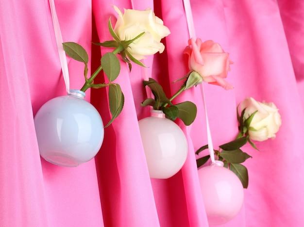 Belles roses dans des vases suspendus à un tissu