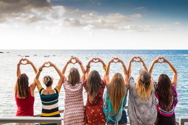 Belles sept filles de l'arrière faisant un coeur avec les mains regardant l'océan