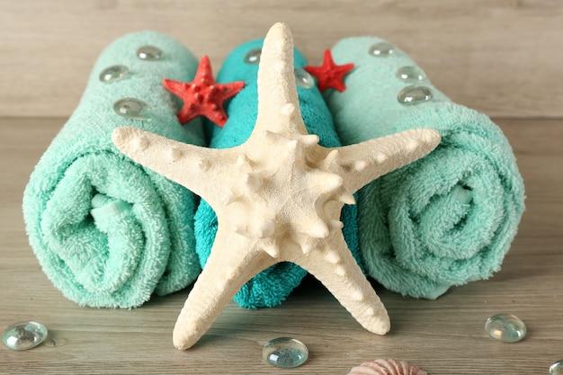 Belles serviettes avec des étoiles de mer et des pierres décoratives sur une surface en bois